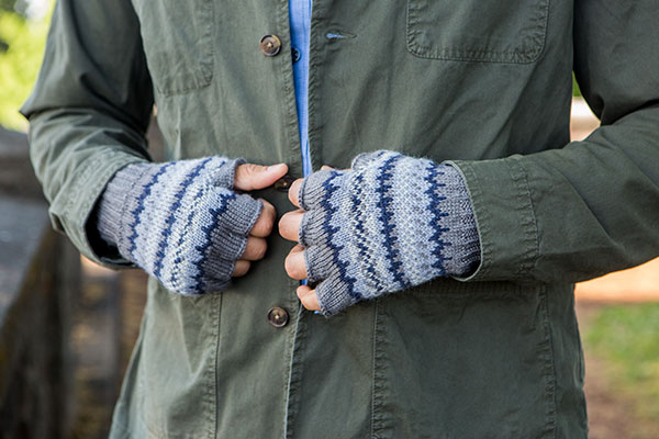 A close up of Jenny Williams' Rye's Stranded Mitts pattern. A model is shown wearing fingerless gloves with stranded colorwork in shades of blue and gray.