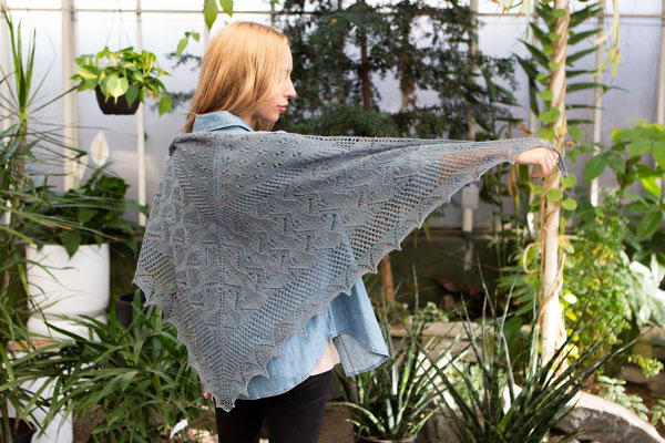 The Jardins Des Fleurs shawl. A model stands with her back to the camera, holding her arm out to display a lacy gray shawl.