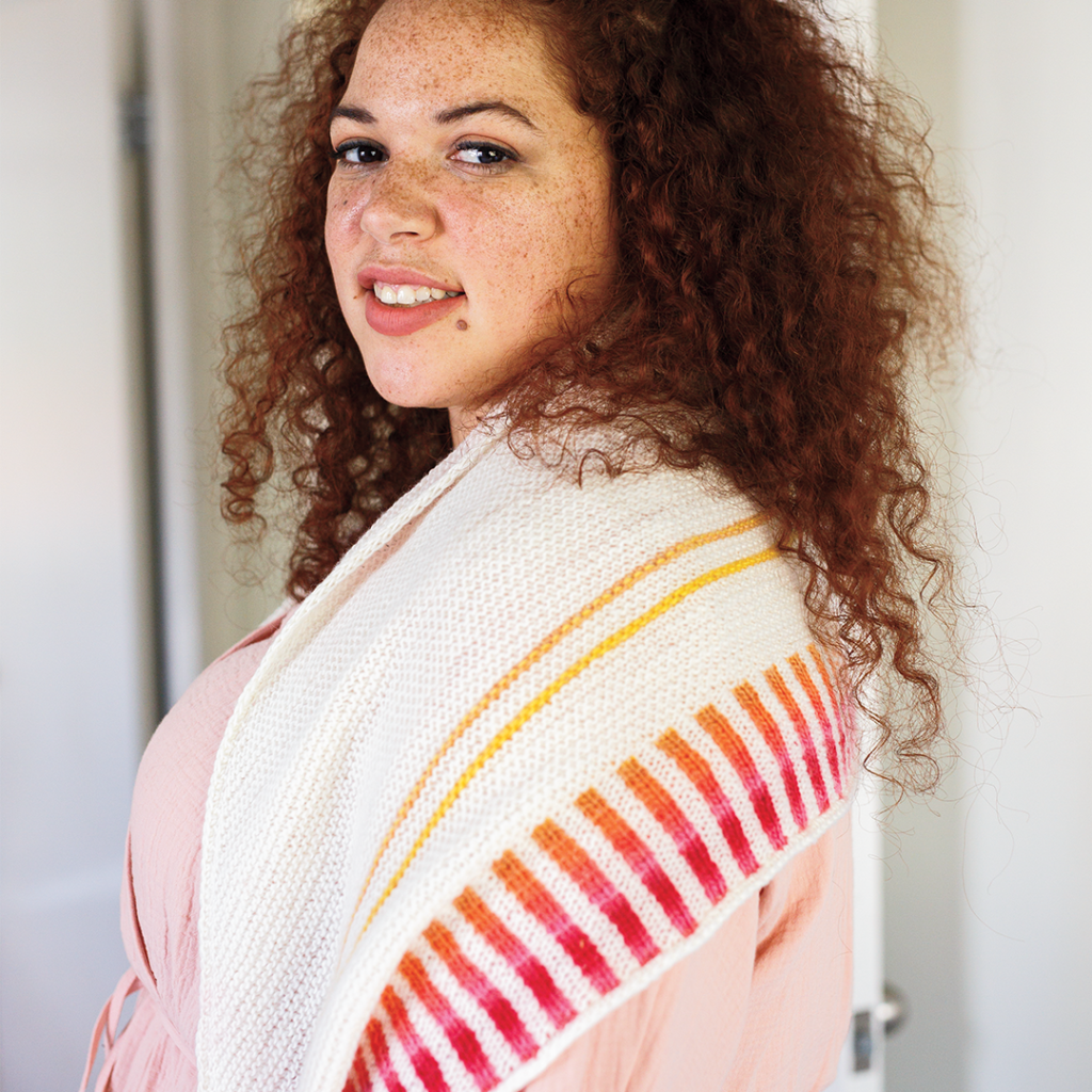 A model wears a cream knitted shaw with yellow-orange-pink-red striped accents.