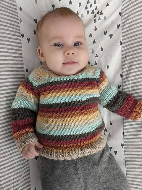 Flax sweater by Ravelry User Vyndree. A baby wears a striped knitted sweater.