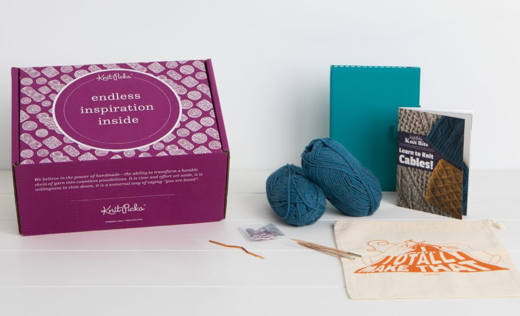 The contents of a boxed knitting kit including 2 balls of blue wool yarn, a Learn to Knit Cables! book, needle tips cable needle, teal chart keeper, and canvas project bag.