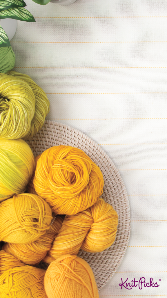 A top-down view of a tablecloth with assorted houseplants and yellow yarn, with the Knit Picks logo at the bottom.